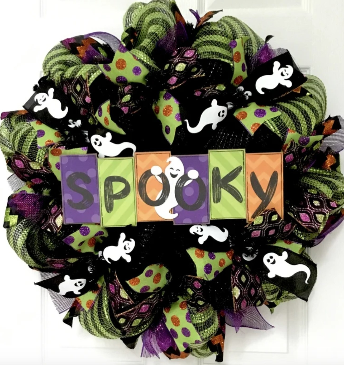"""The mesh green purple and orange wreath has sparkles, ghosts, stripes, polka dots and a sign that says """"SPOOKY"""""""
