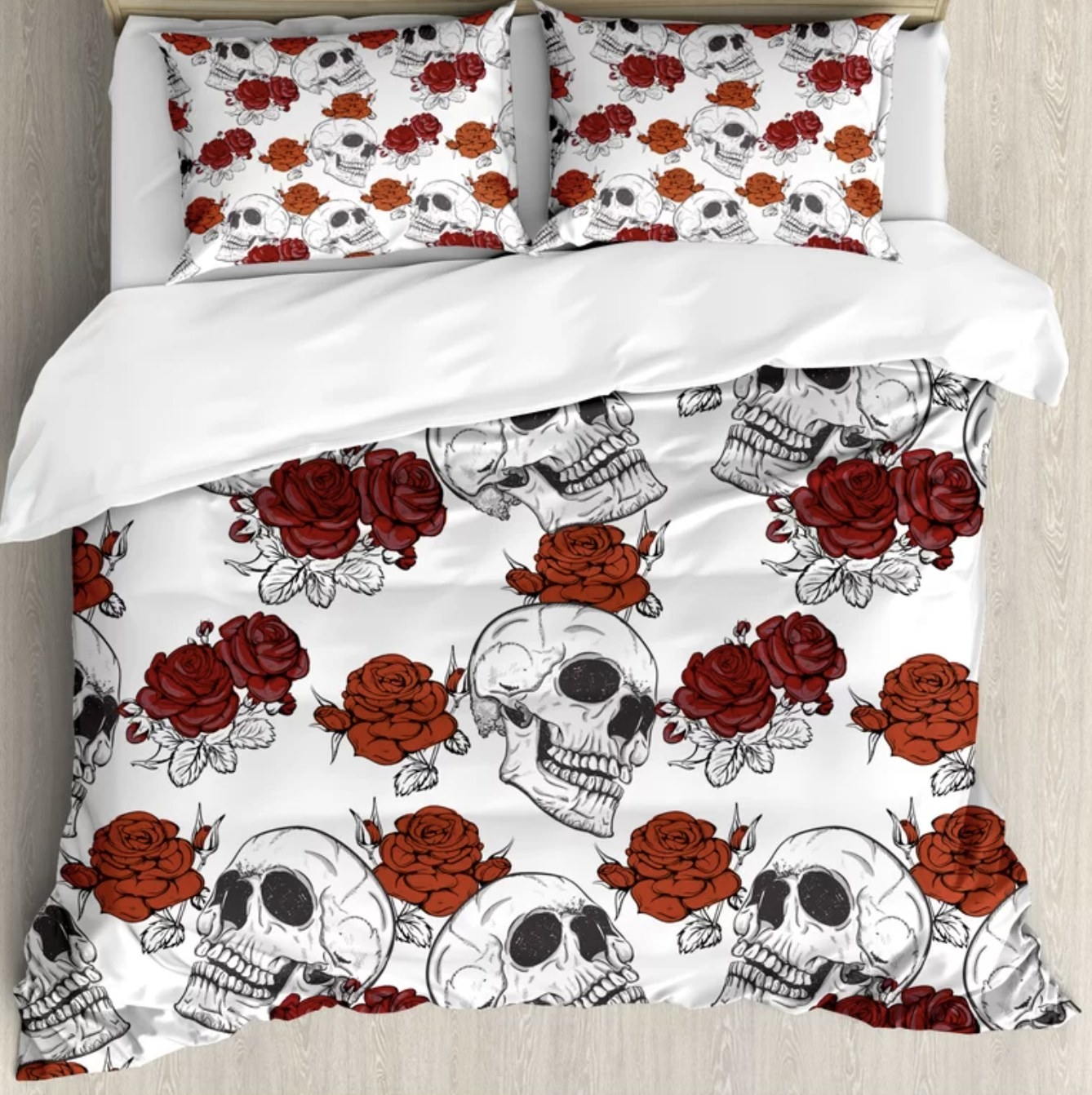 The white pillow shams and duvet covers have large skulls and red roses