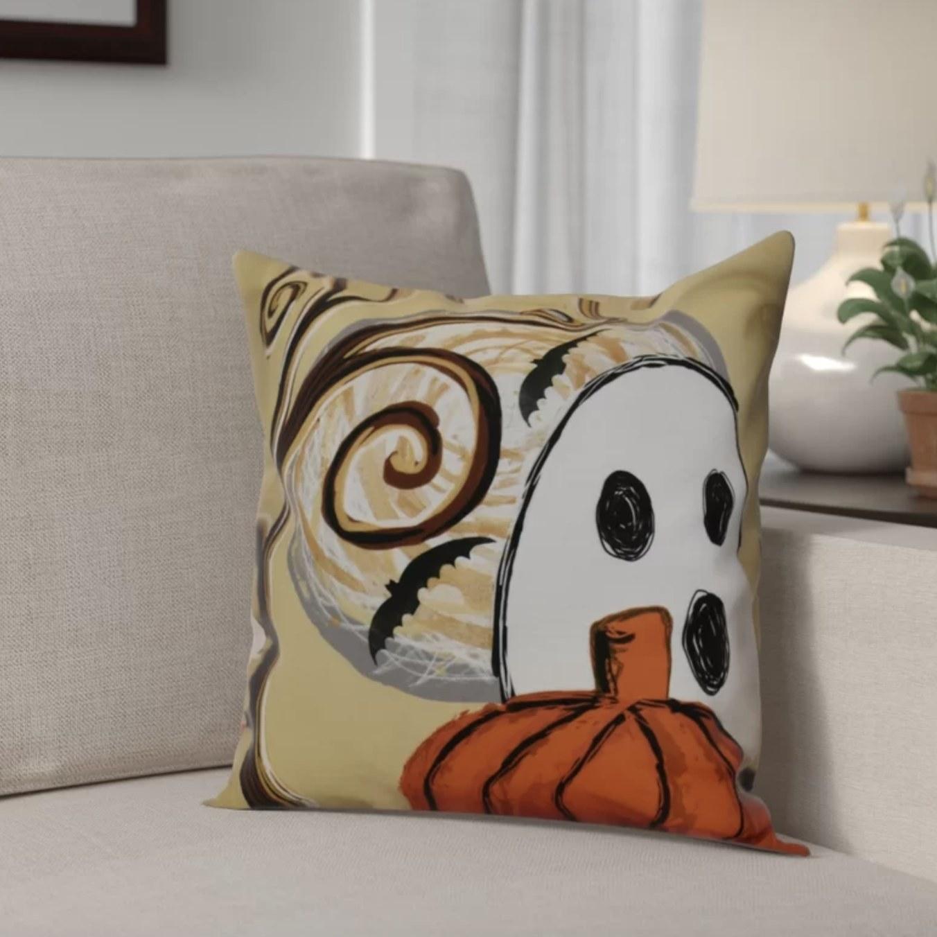 The gold pillow has a ghost, pumpkin, bats and dark swirls