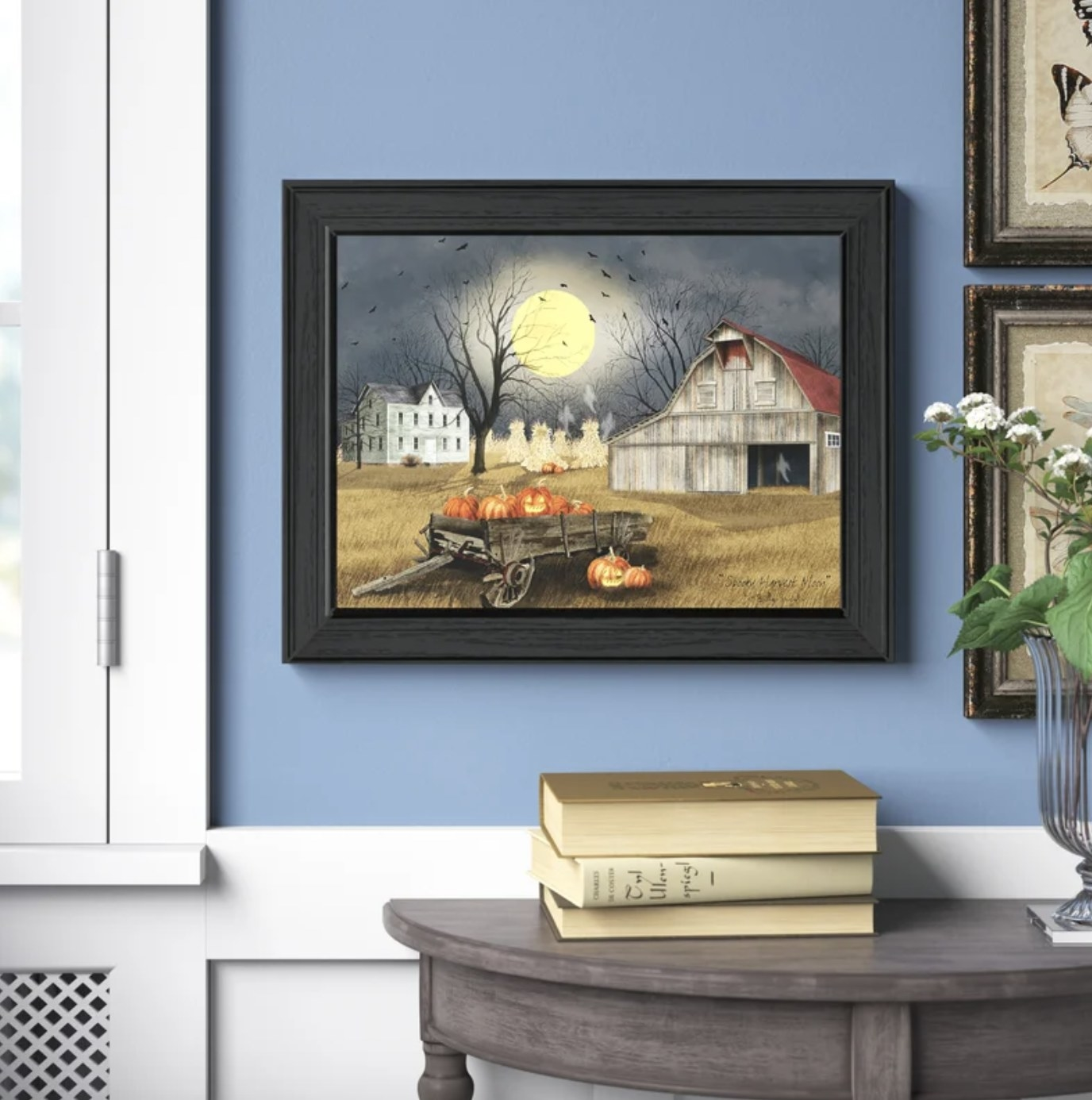 The harvest moon painting has a barn, trees with bare branches, a wagon full of pumpkins, bats and various other spooky elements