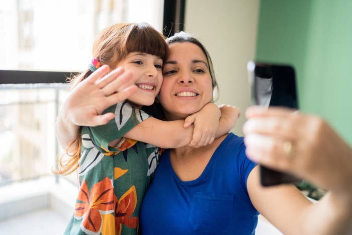 Smiling young girl embracing a smiling woman, who's taking a selfie