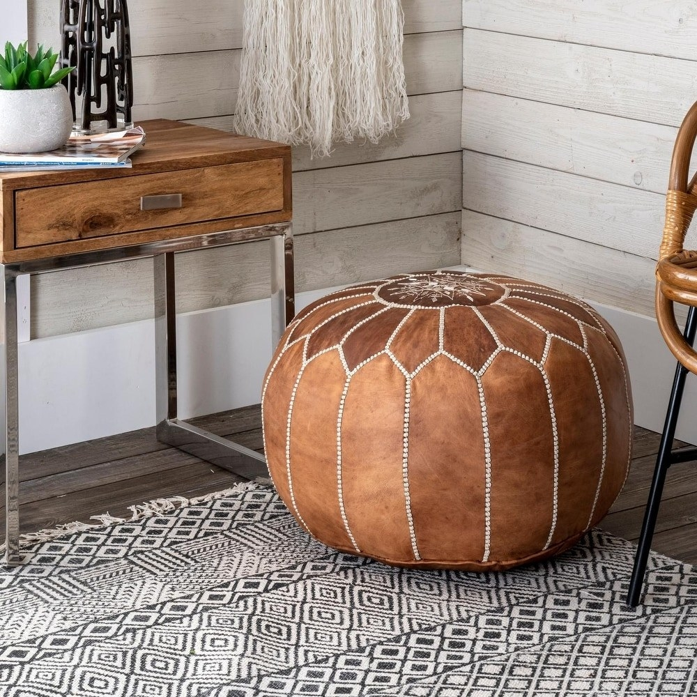 A brown pouf ottoman with a stitched design