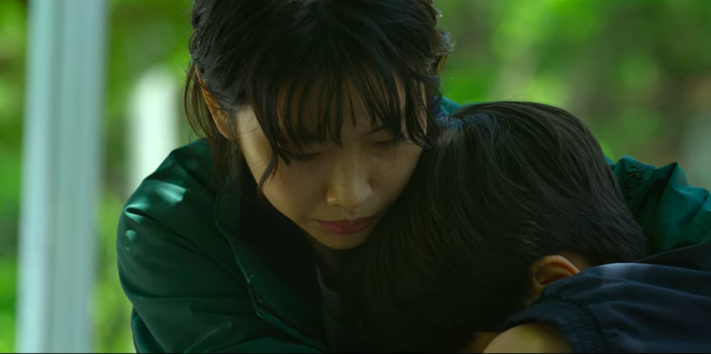 Sae-byeok looking down and hugging someone else