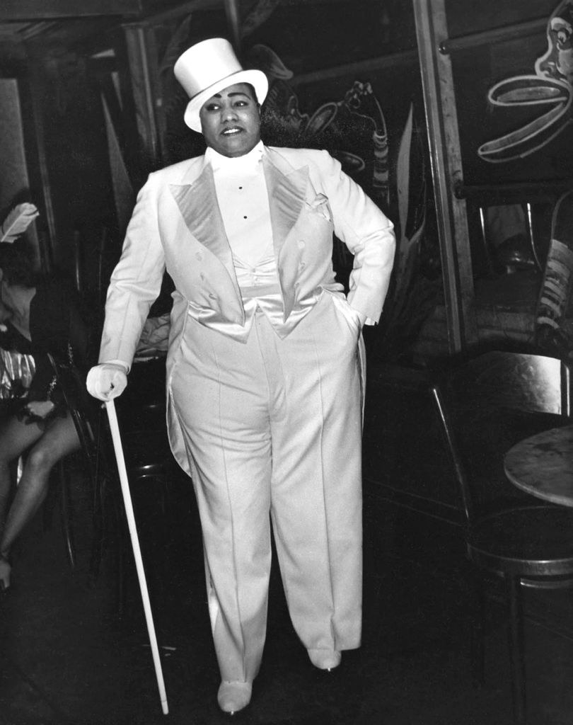 Gladys Bentley standing in men's clothing backstage