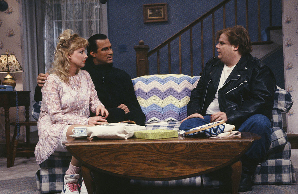 Steven Seagal seated across from Chris Farley in a living room