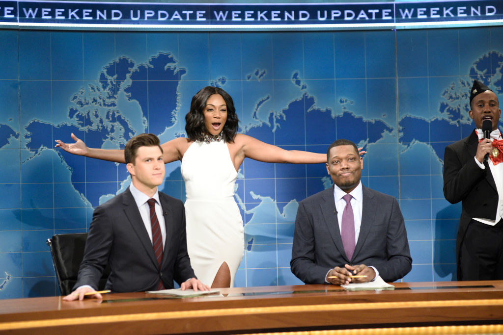 Tiffany Haddish crossing through the background of Weekend Update in a white gown