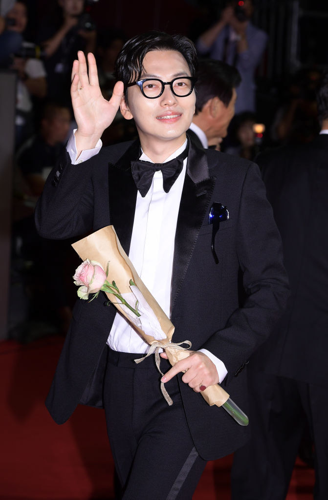 Dong-hwi Lee in a bow tie, waving and holding a flower on the red carpet