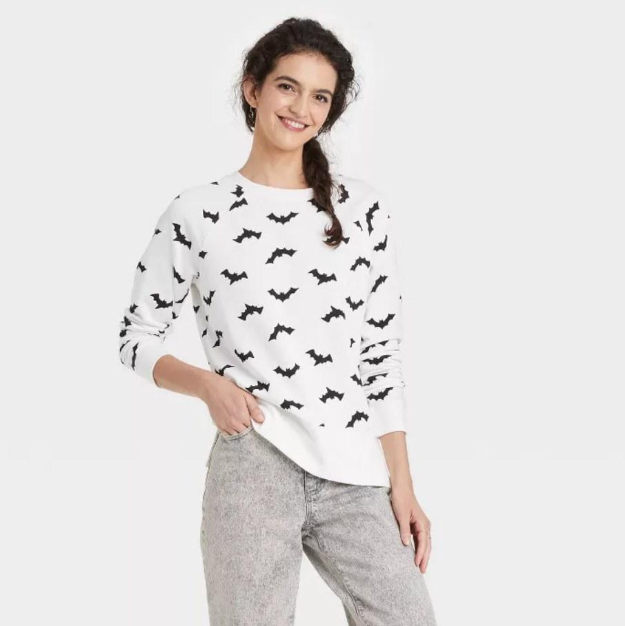 a model wearing the sweatshirt in white with black bats