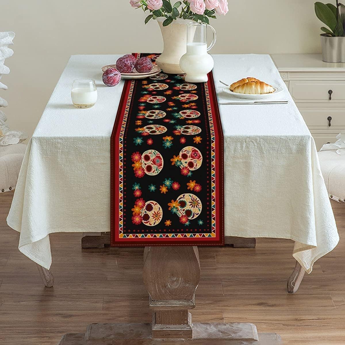 Camino de mesa con patrones de calaveras de azúcar