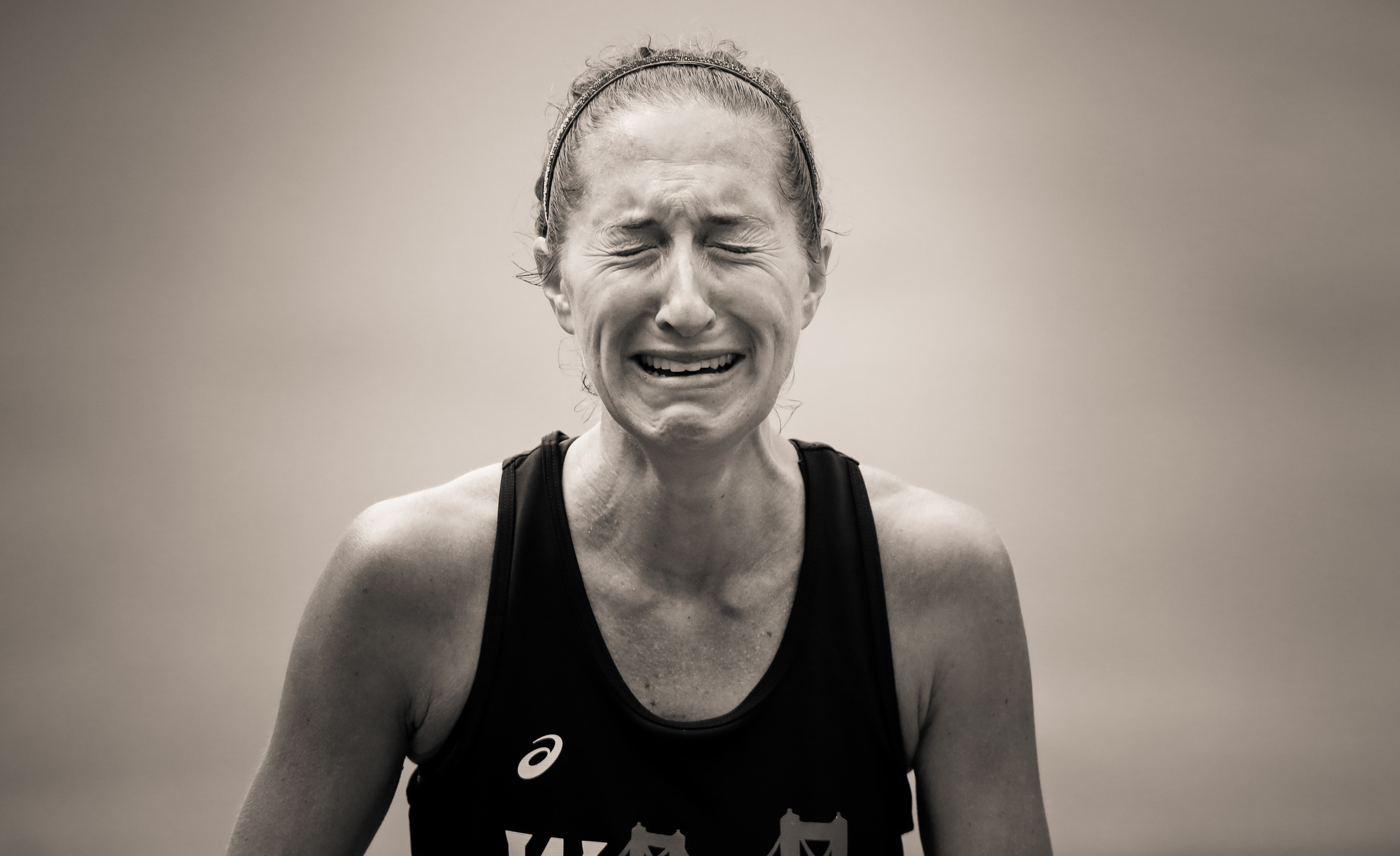 A woman's face is contorted with tears as she finishes the marathon