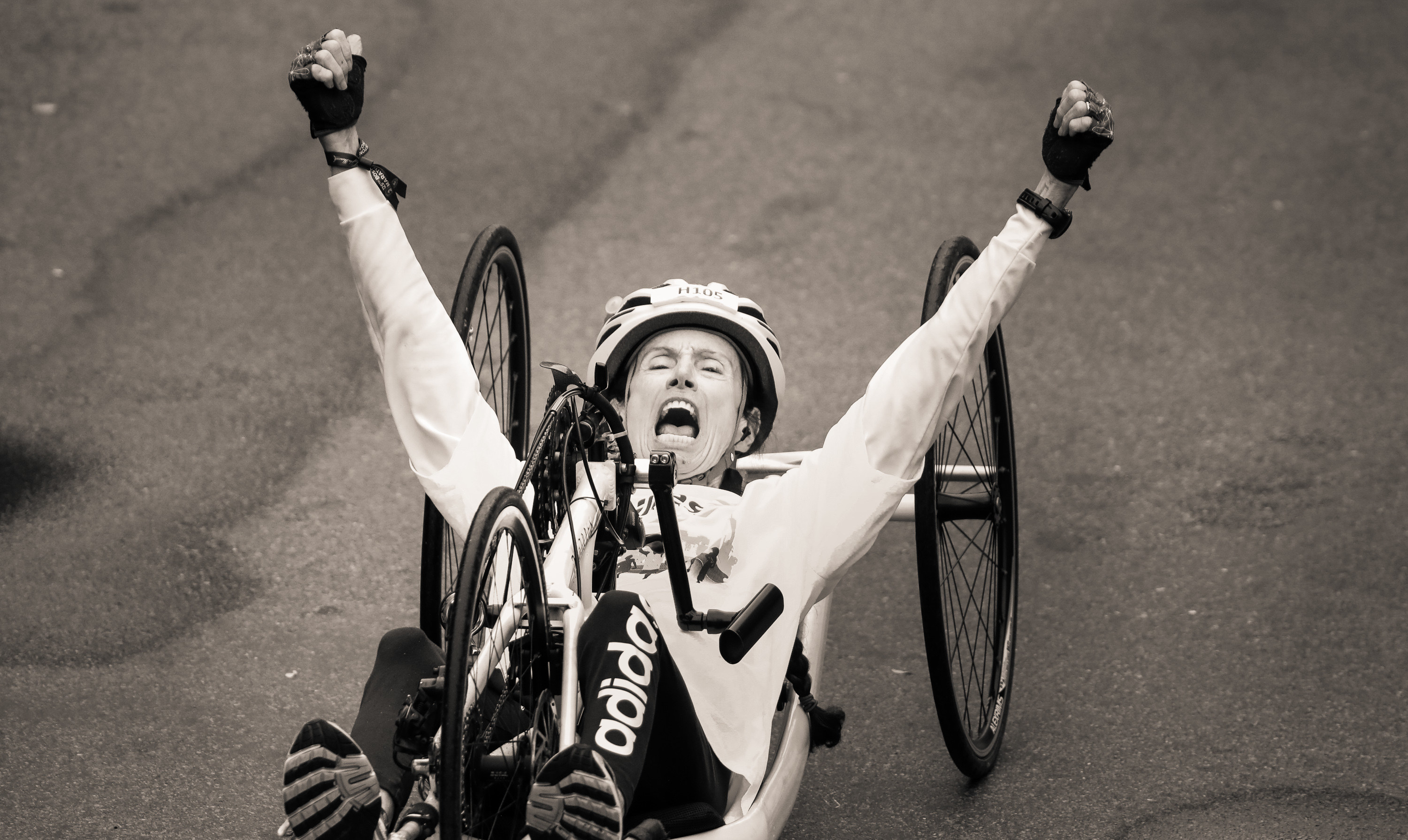 A competitor in a recumbent bicycle celebrates as he crosses the finish line