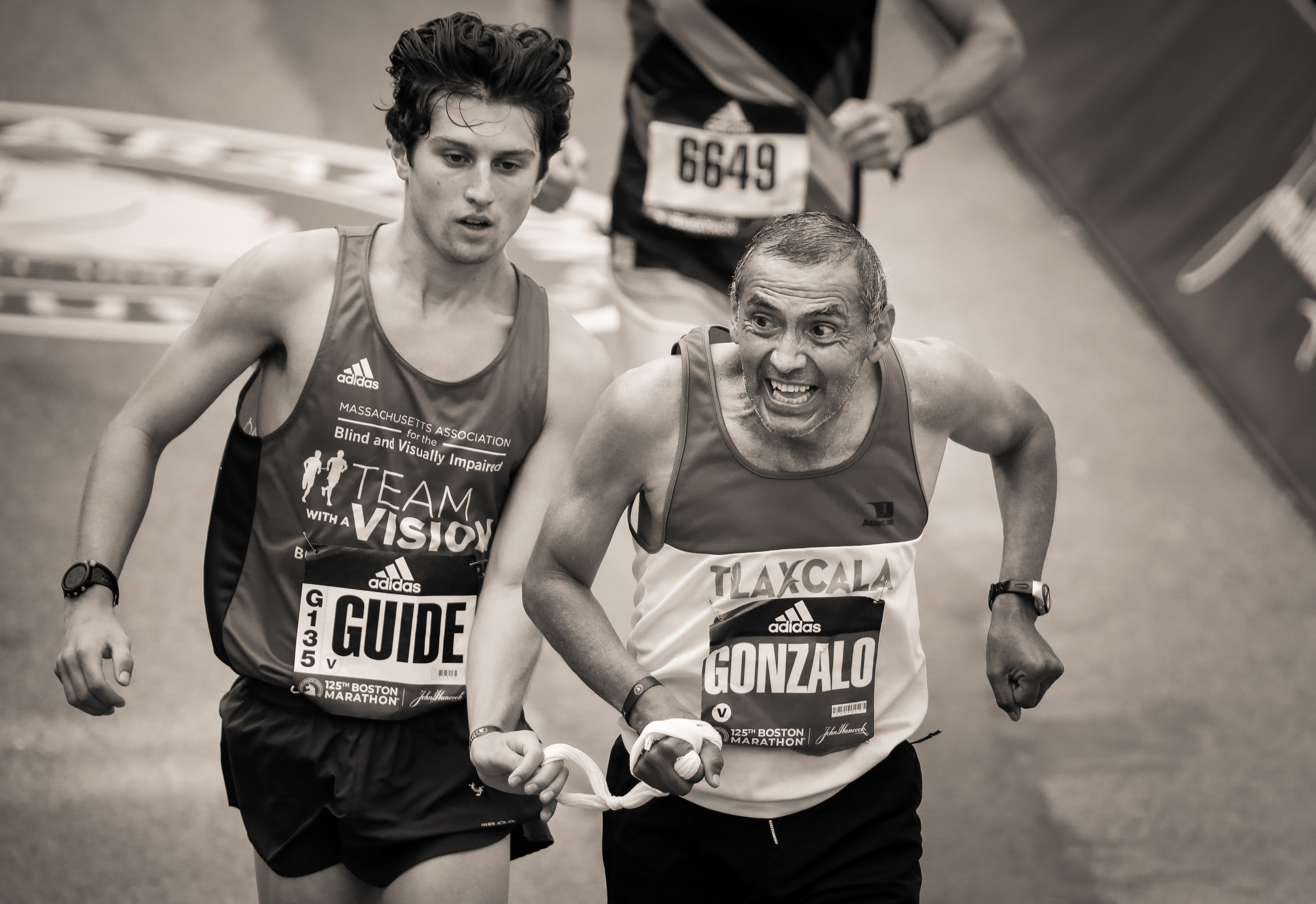 A visually impaired runner and guide cross the finish line