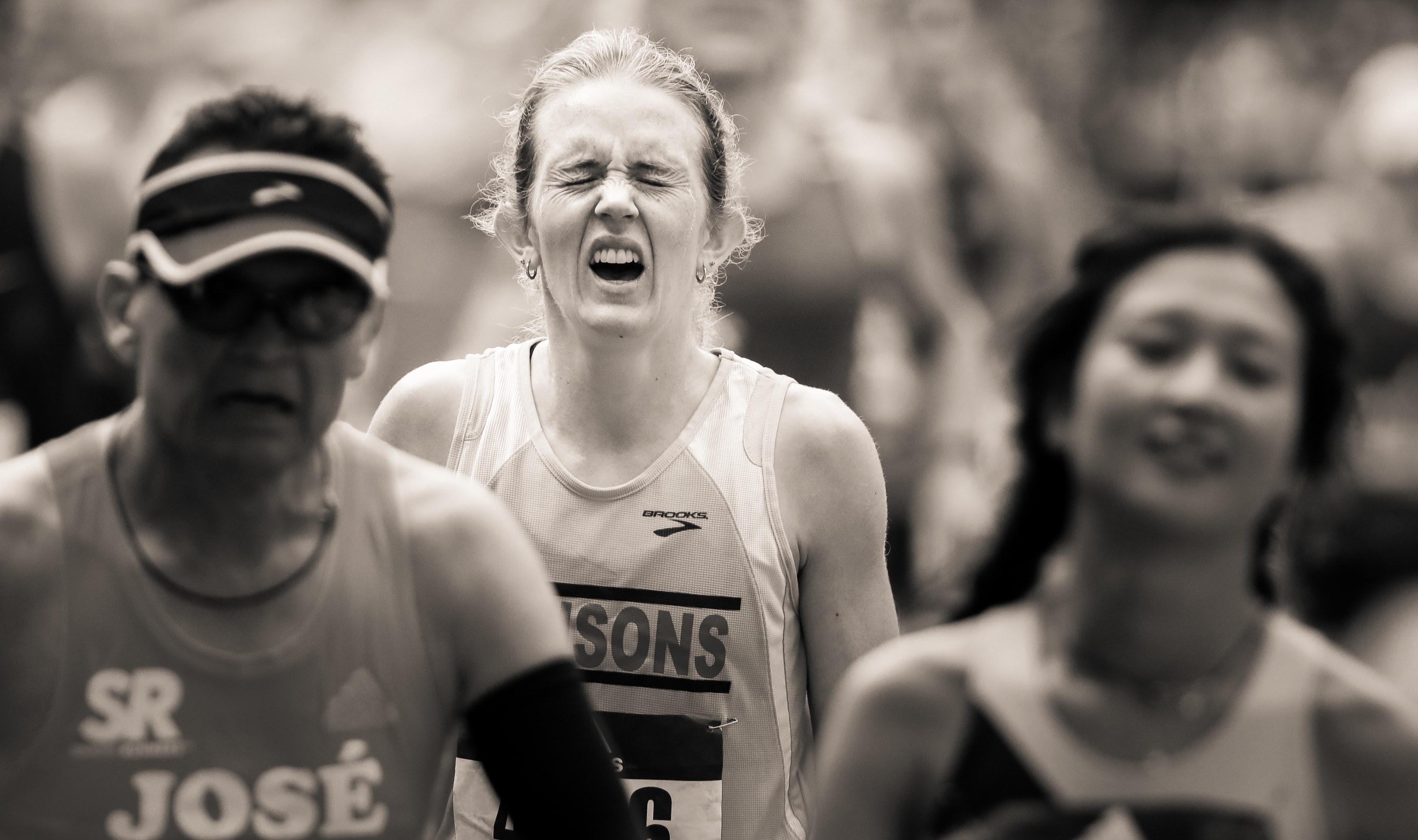 A woman grimaces through a crowd as she crosses the finish line