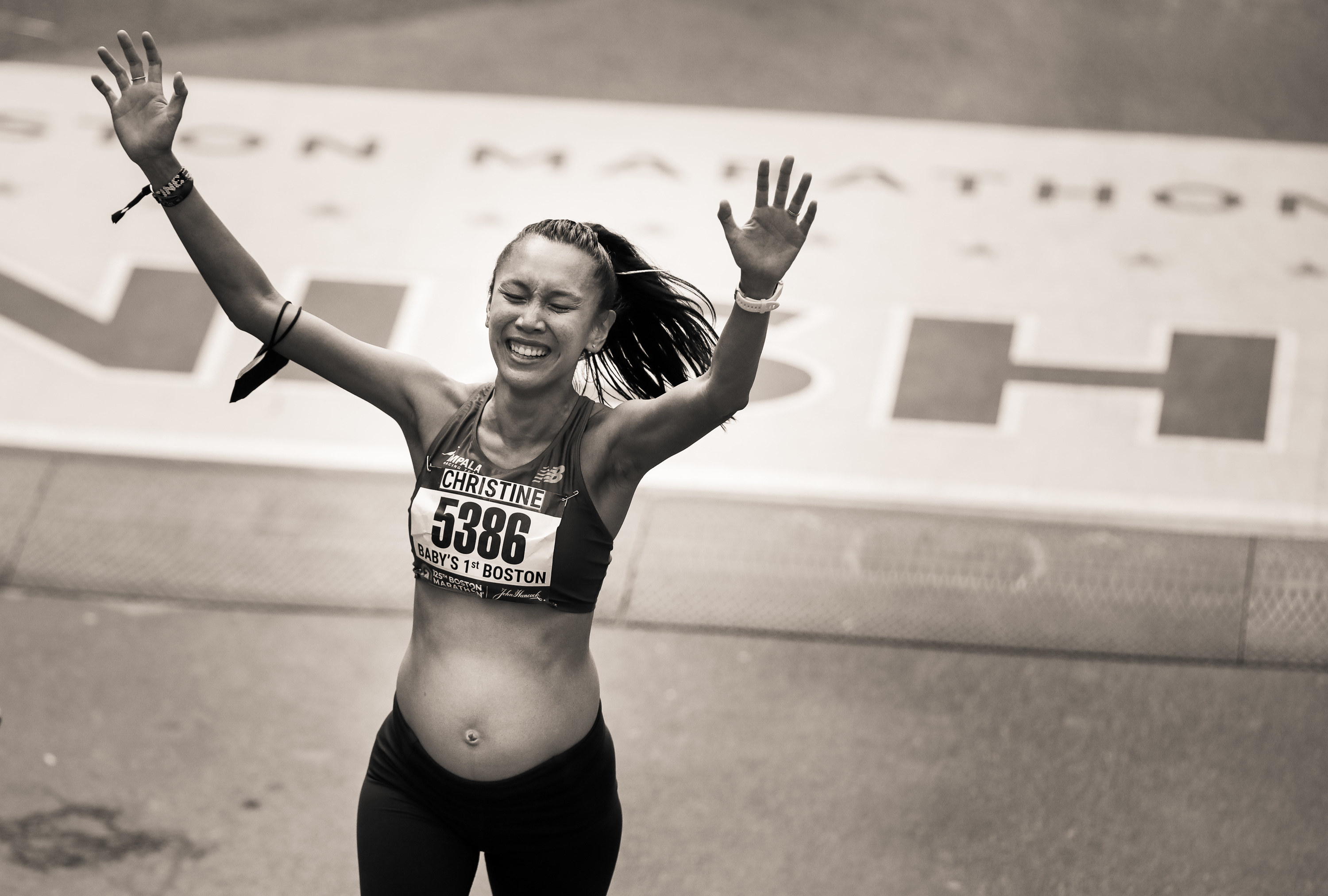 A visibly pregnant woman crosses the finish line with her arms raised.