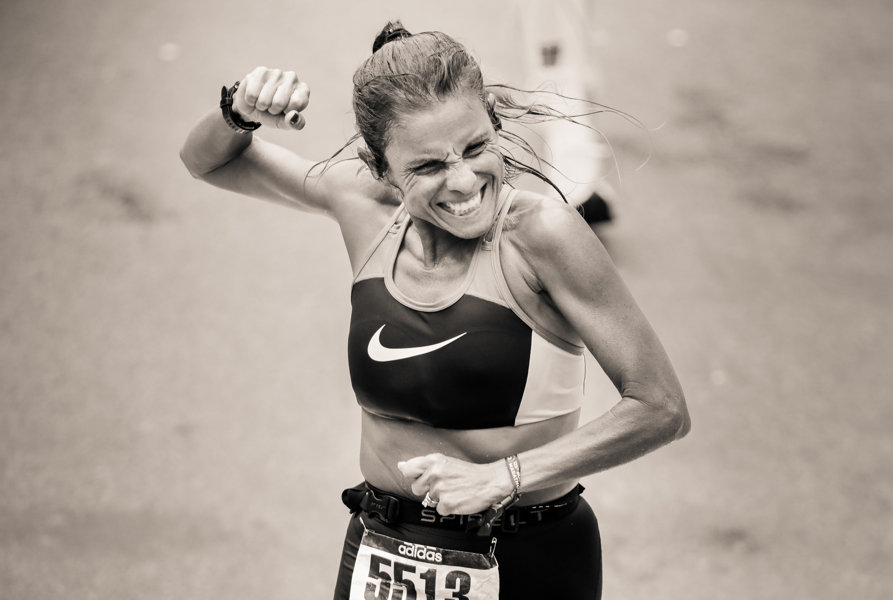 A woman pumps her fist as she crosses the finish line of the Boston Marathon