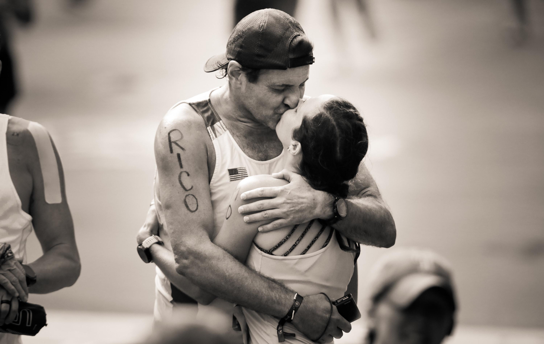 A couple kiss at the finish line of the Boston Marathon