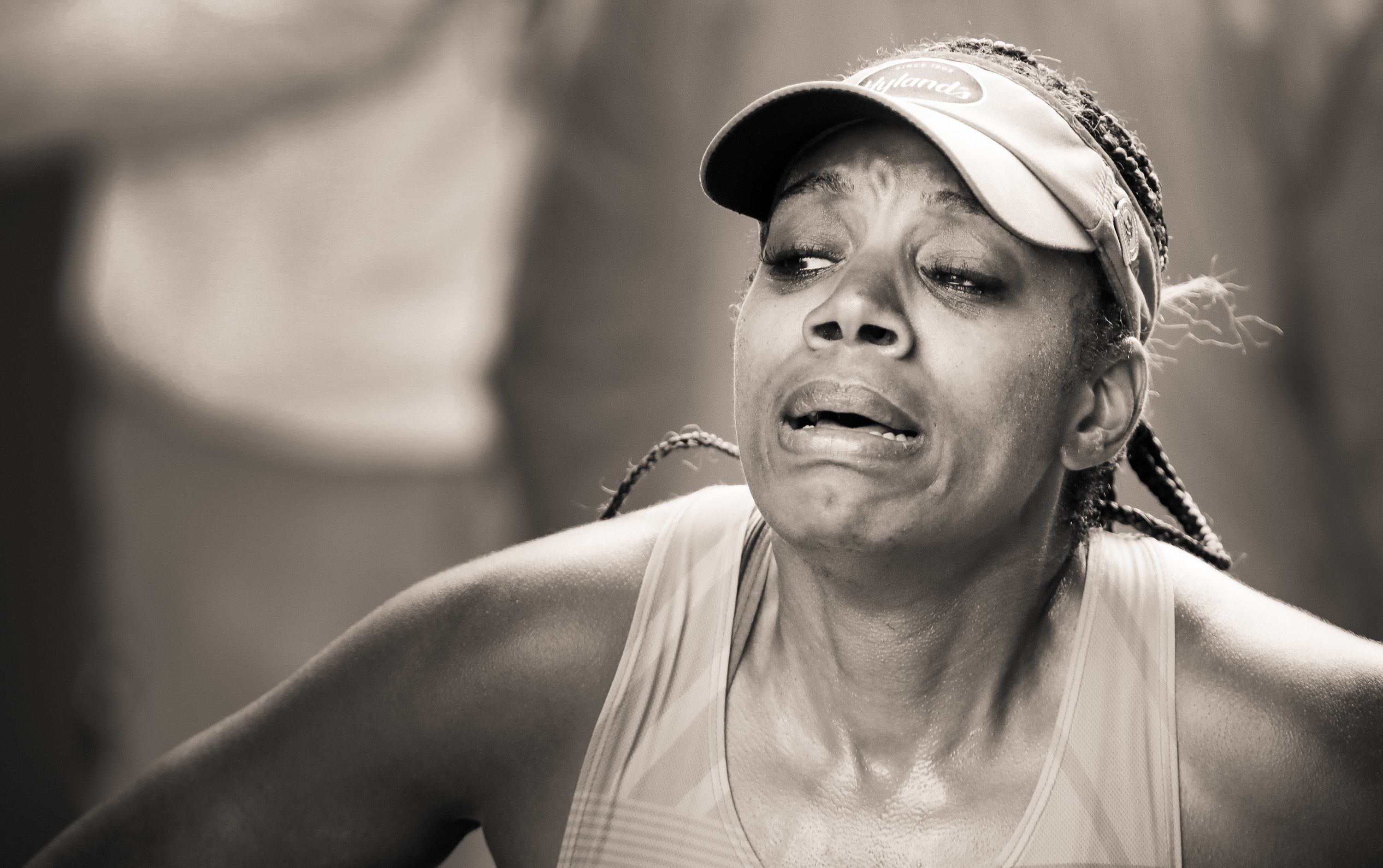 a woman grimaces at the end of the marathon