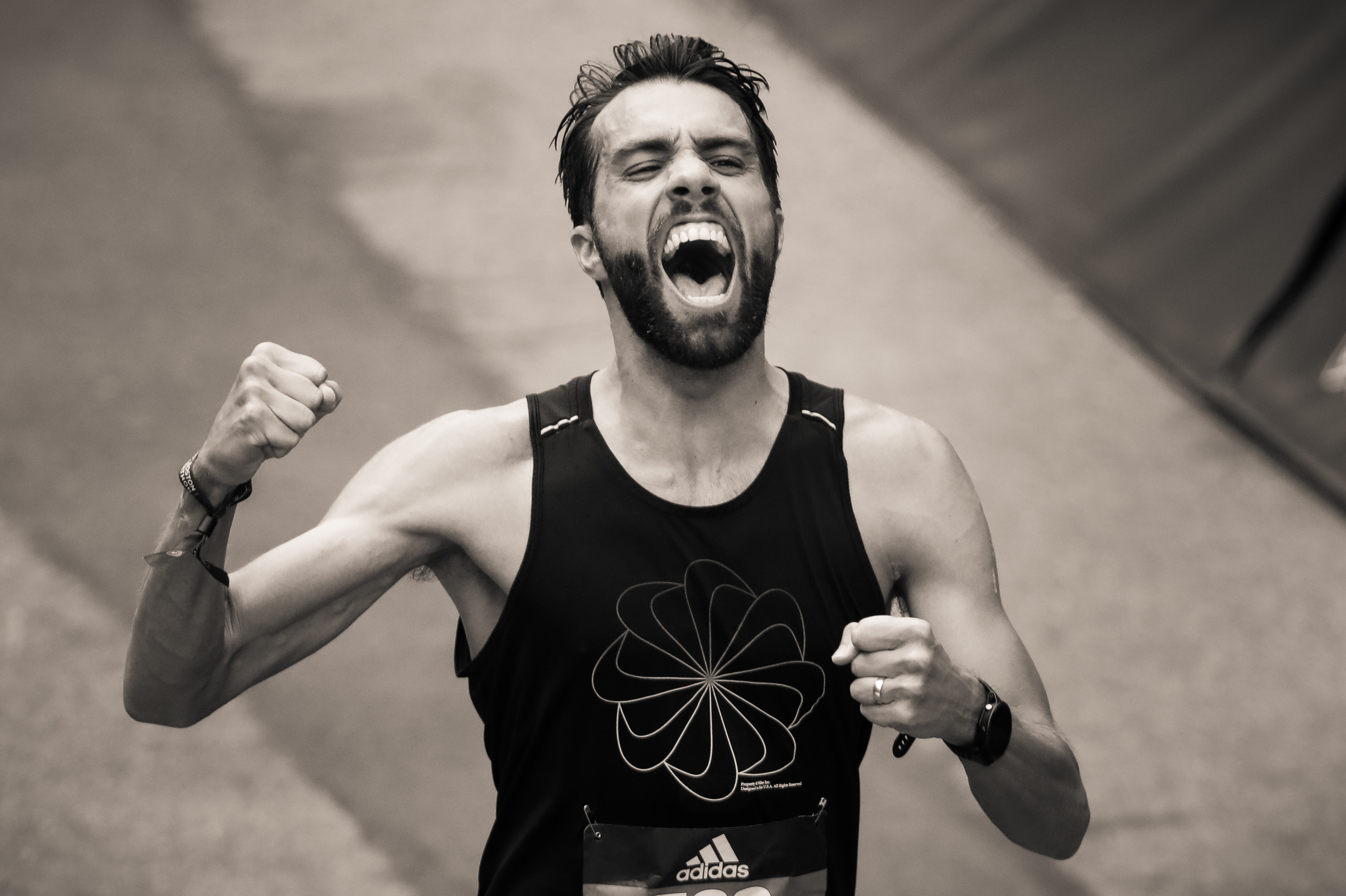 A man pumps his fist crossing the finish line