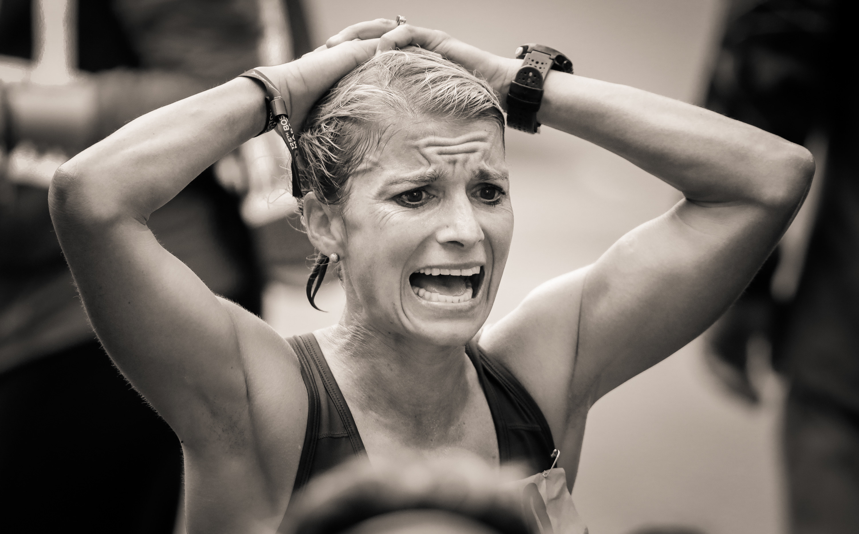A woman grimaces at the finish line