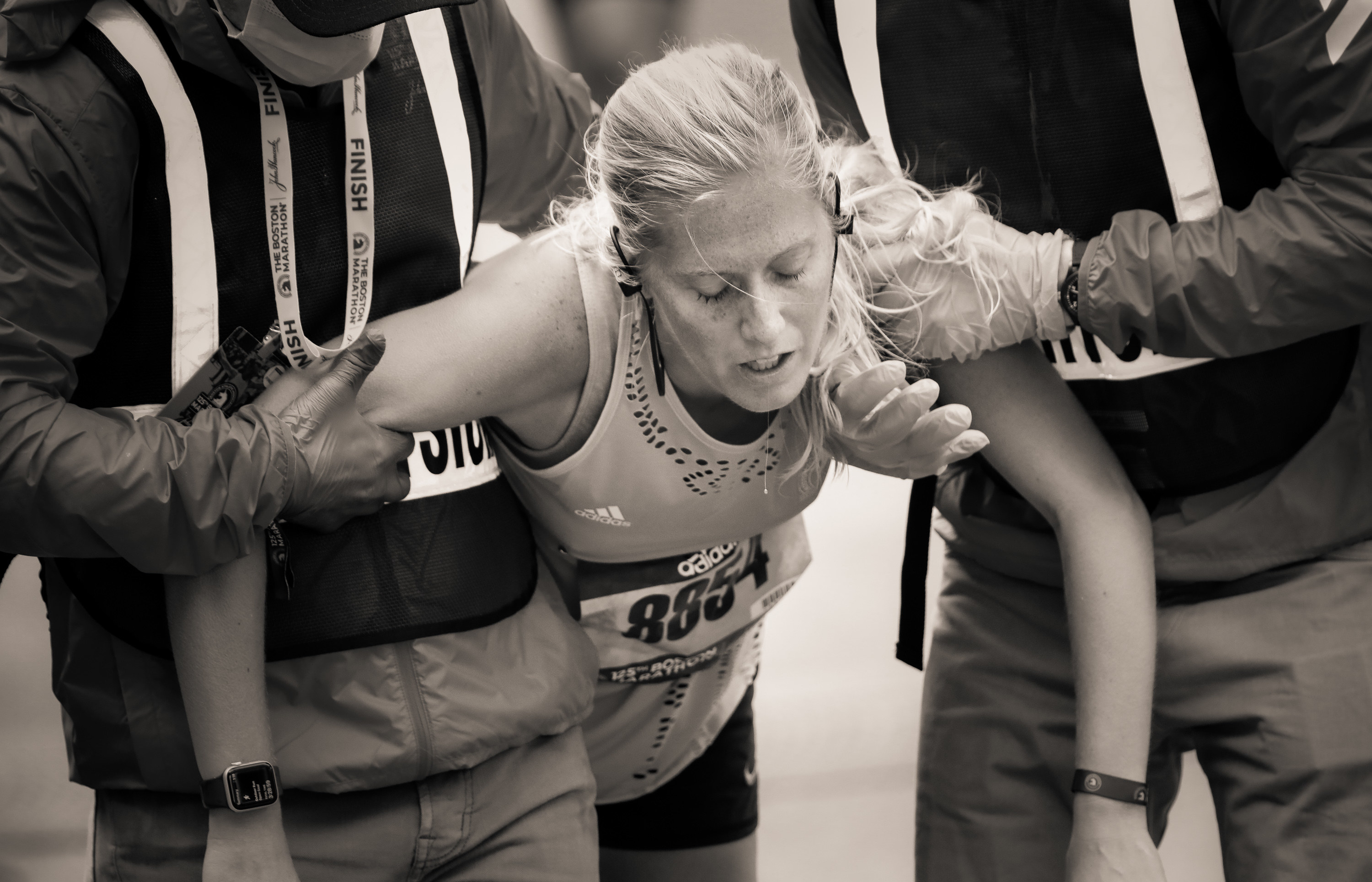 Two race attendants help a woman who has nearly collapsed at the marathon