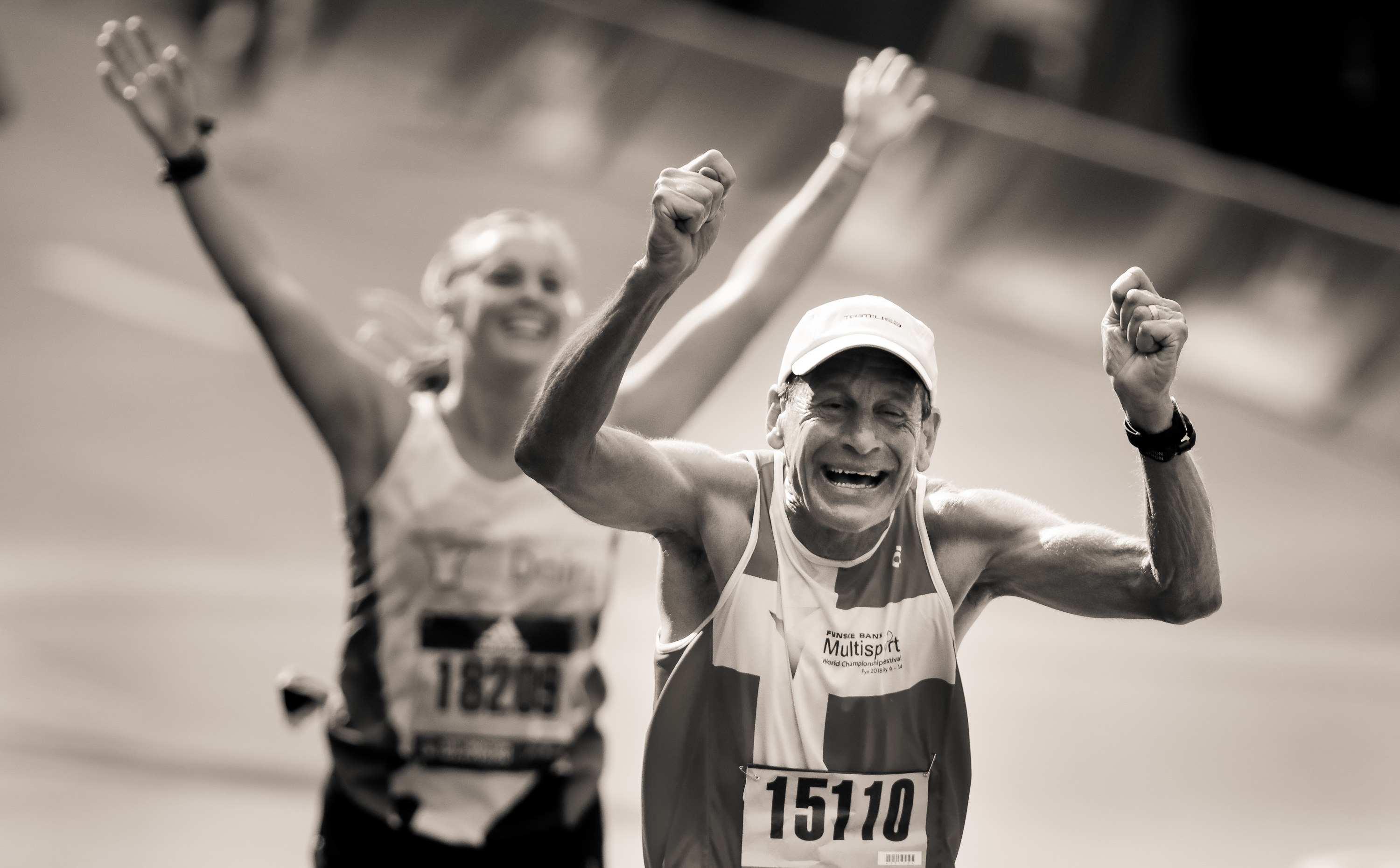 An older man cheers at the finish line, a woman celebrates behind him
