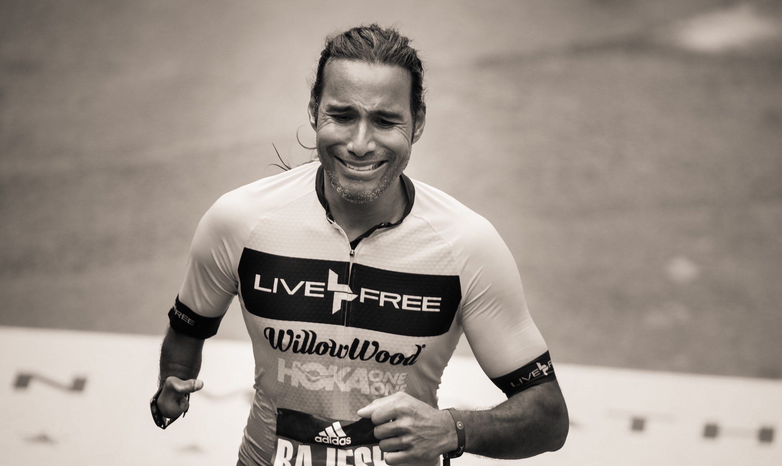 A man smiles as he crosses the finish line