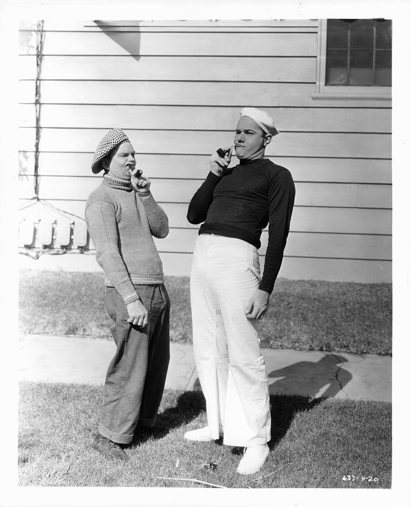 Haines smoking with a costar while wearing a sailor's outfit