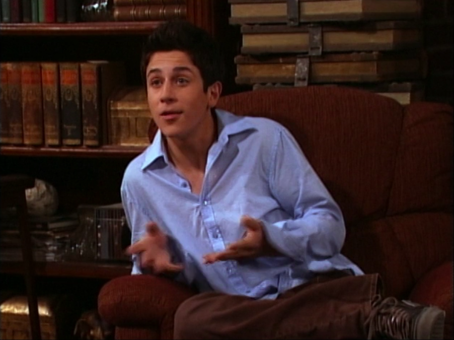 David Henrie as Justin Russo sits on a chair in a button down shirt