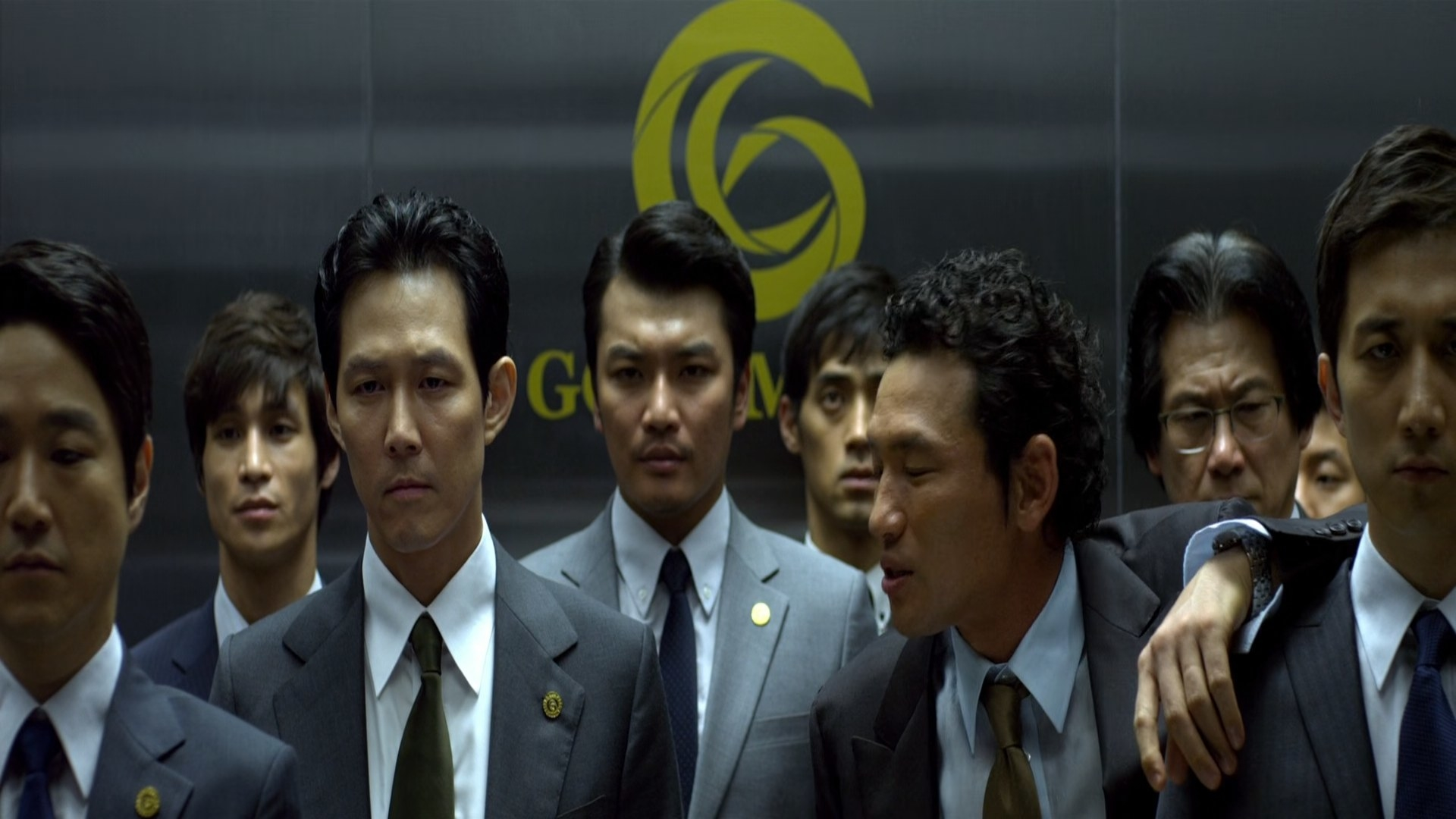 A group of men standing in an elevator.