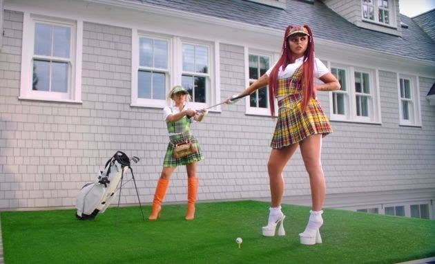 Jesy being handed a golf club while wearing a polo and plaid vest and skirt