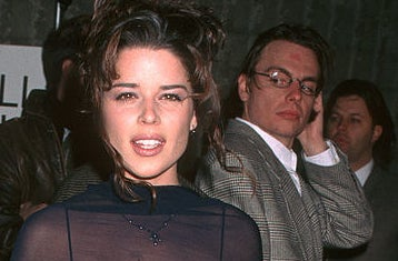 A man checking out Neve Campbell on the red carpet
