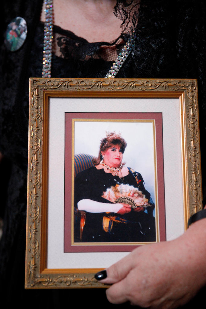a mourner carries a portrait of Sarria at his funeral