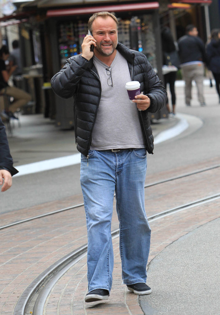 David DeLuise walking outside, talking on the phone, and holding a coffee cup