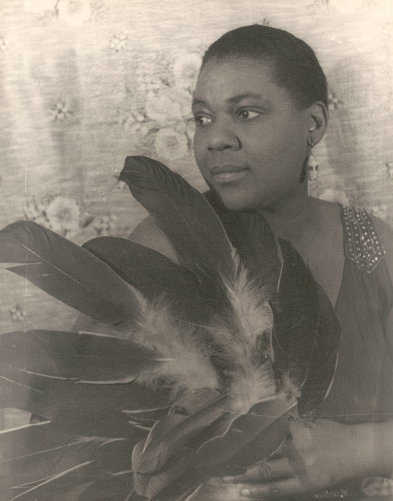 a portrait of Bessie holding a bundle of feathers
