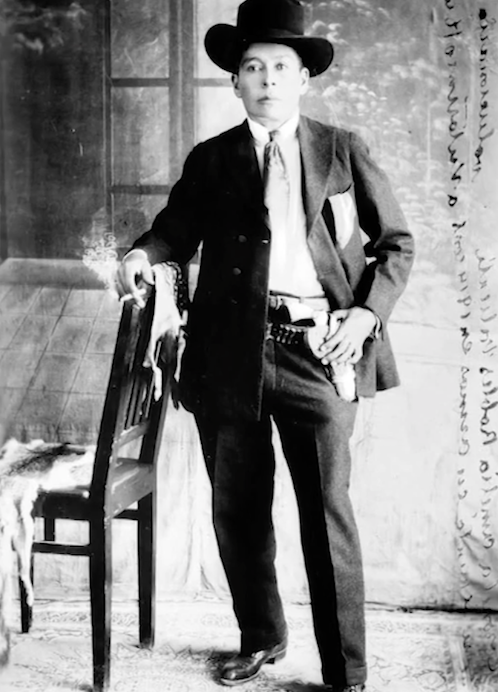A portrait of Avila, with his hand on his gun