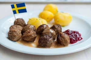 a plate of swedish meatballs with a little swedish flag in them