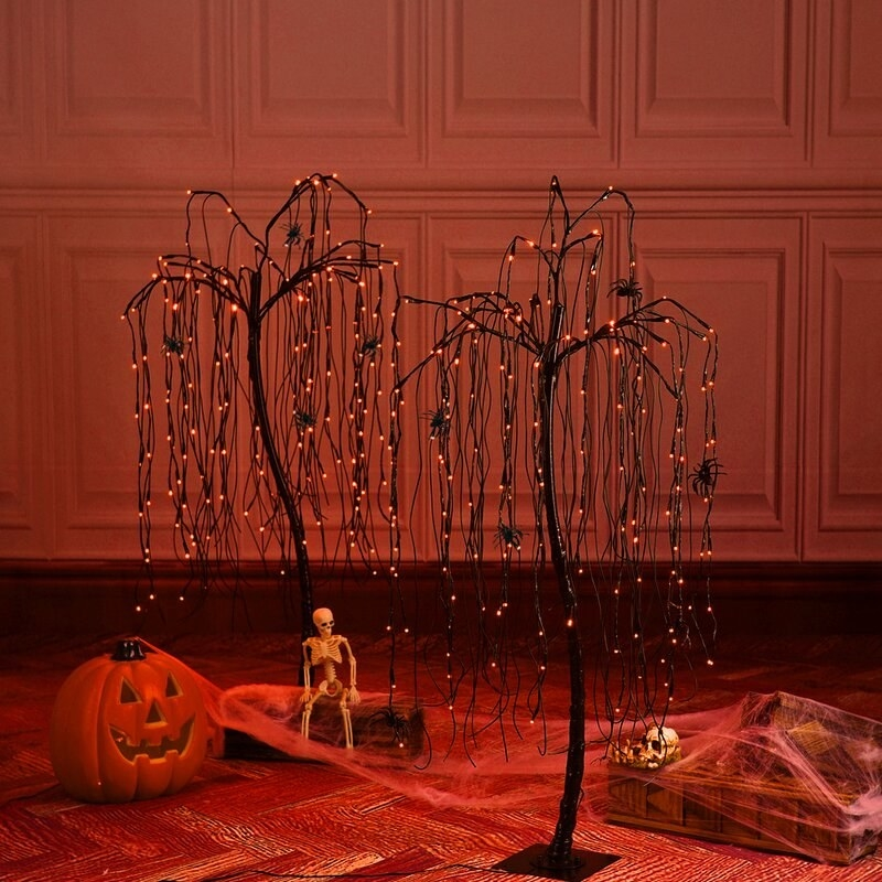 a pair of black light up willow trees with orange lights