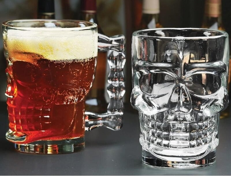 the two skull mugs, one empty and one with beer in it