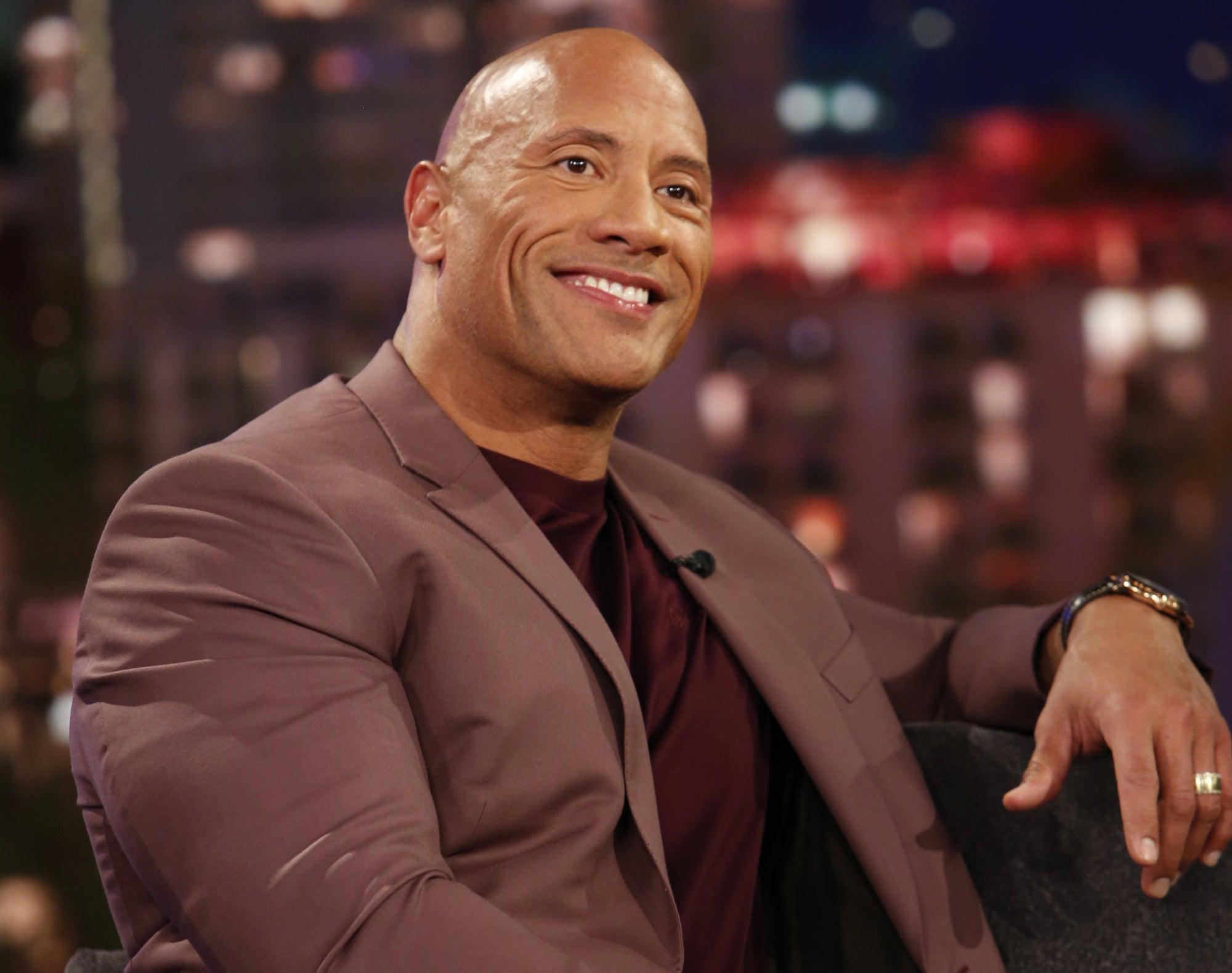 Dwayne Johnson smiles on a night show.