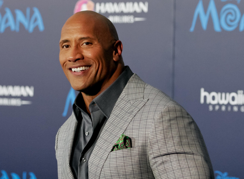 Dwayne Johnson smiles at a movie premiere.