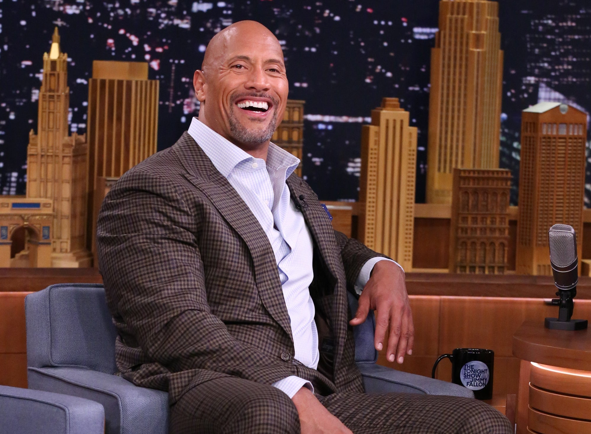 Dwayne laughs while on set at a night show.