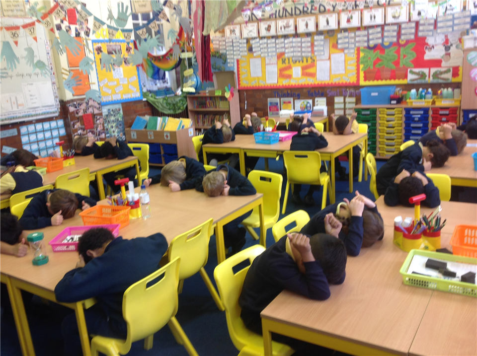 Students in a classroom playing heads down, thumbs up