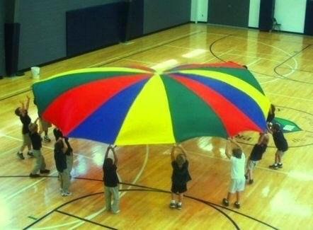 Students lifting a rainbow parachute