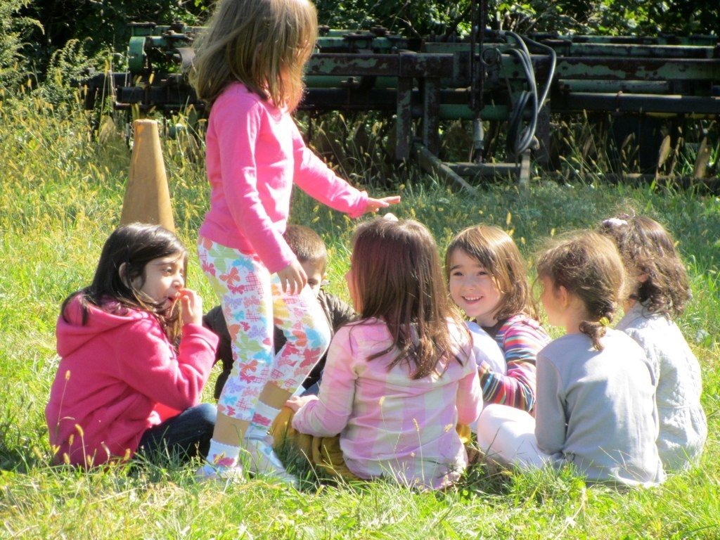 A group of kids playing duck, duck, goose