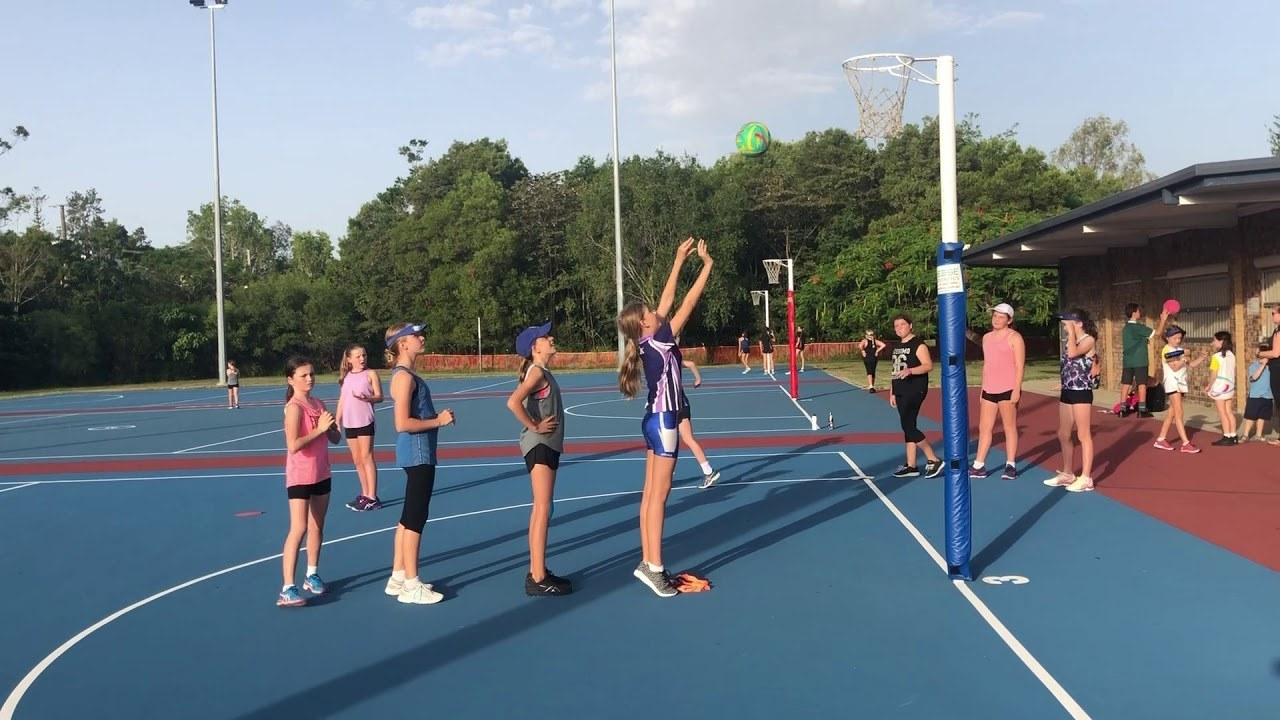 A group of children playing Golden Child on a netball court