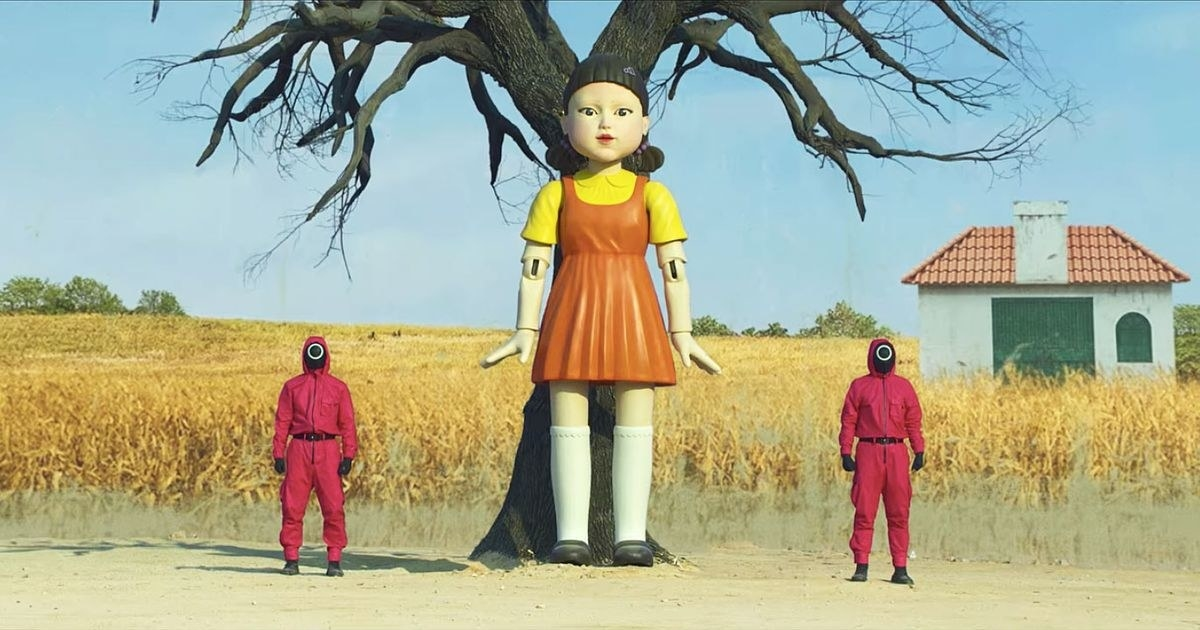 The Red Light, Green Light doll in Squid Game standing in front of a tree; there are two guards standing on either side of her