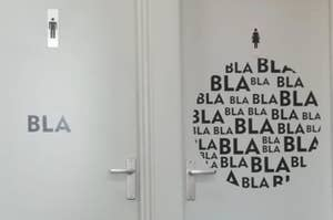 """A men's bathroom that says """"bla"""" and a women's bathroom that says """"blablablablabla"""""""