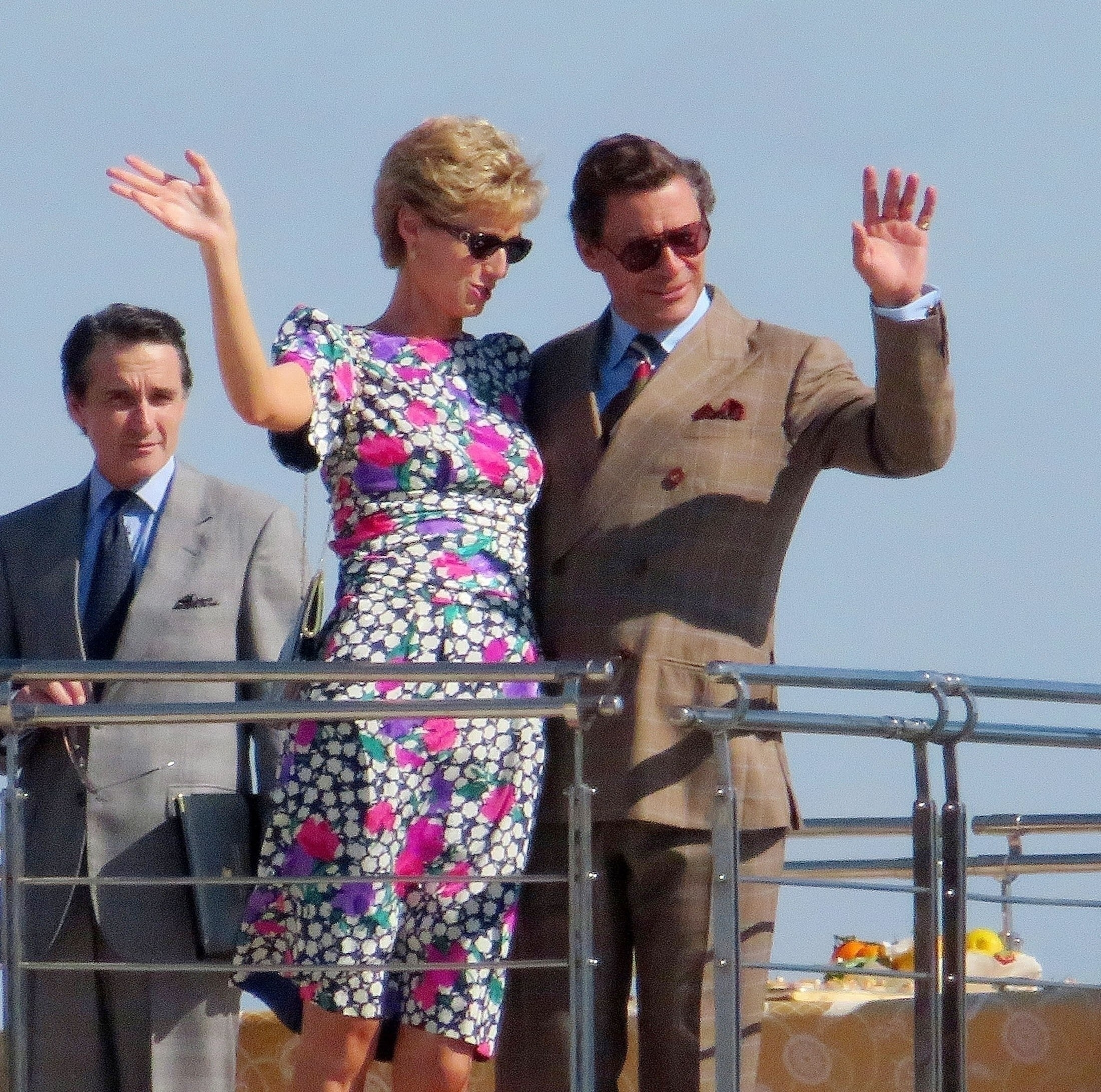 Elizabeth and Dominic waving as they film a scene aboard the yacht