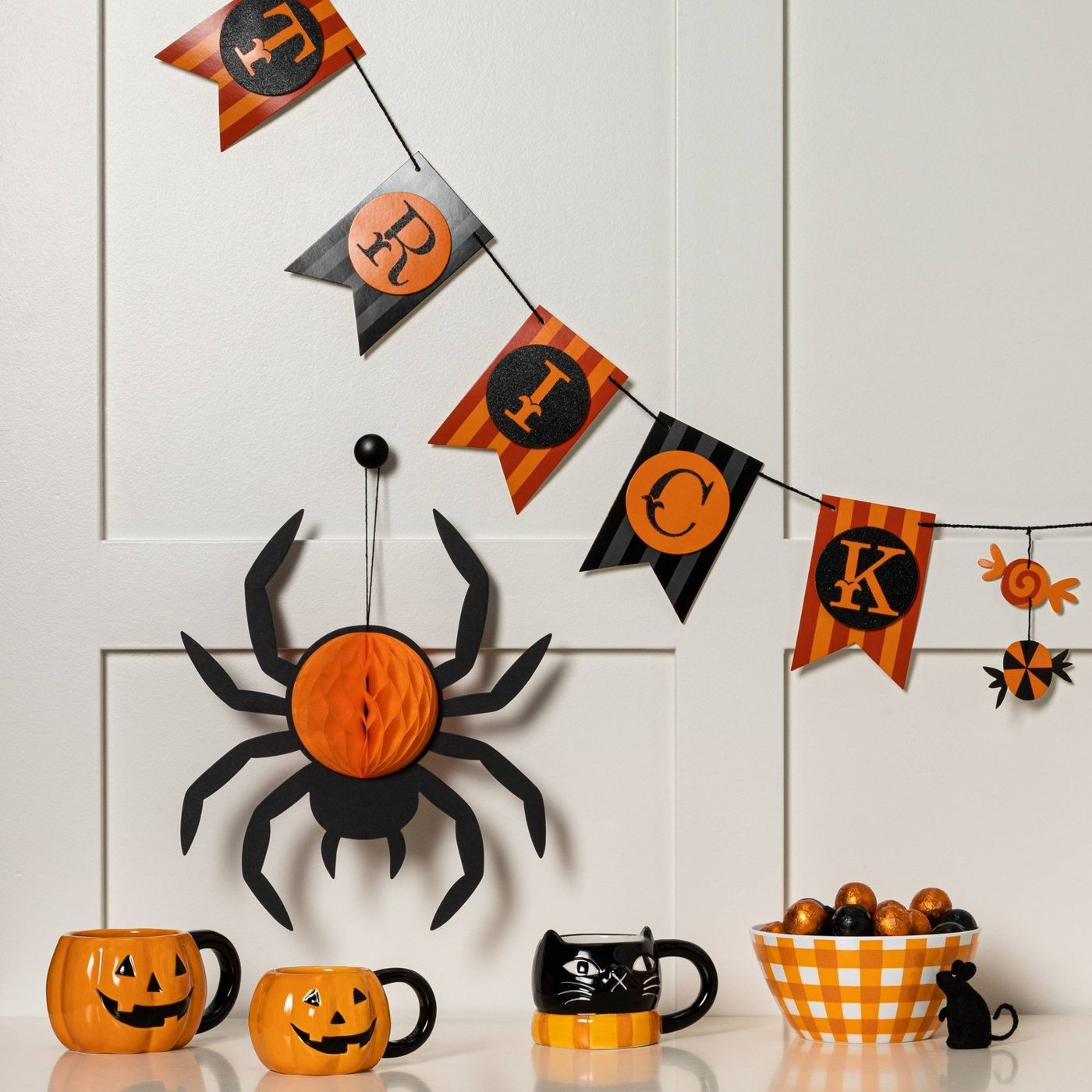 a hanging spider over a table with other halloween decor