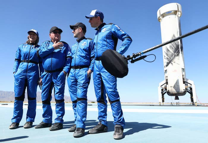 The four crew members standing on the landing pad after their flight